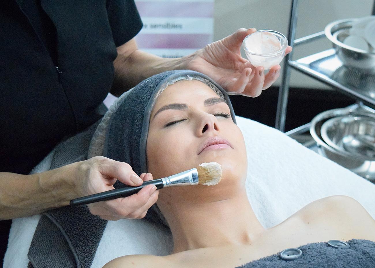 Fille avec soin visage, crème et massage. Institut de Beauté. Terra Lucentum