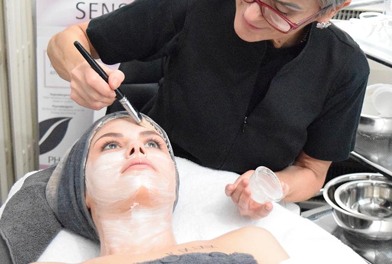 Femme qui applique de la crème sur visage. Institut de beauté